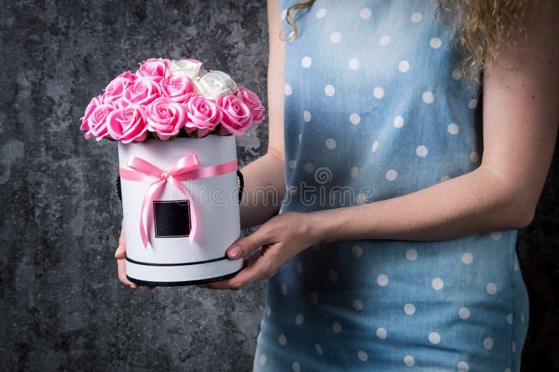 一件蓝色礼服的一个女孩拿着红色和白色,桃红色和白玫瑰花束在帽子箱子的 深灰背景 库存图片