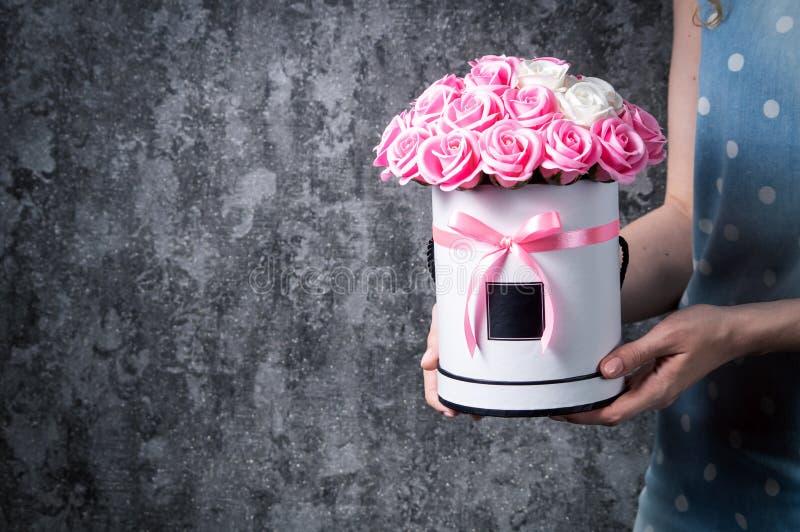 一件蓝色礼服的一个女孩拿着红色和白色,桃红色和白玫瑰花束在帽子箱子的 深灰背景 免版税图库摄影