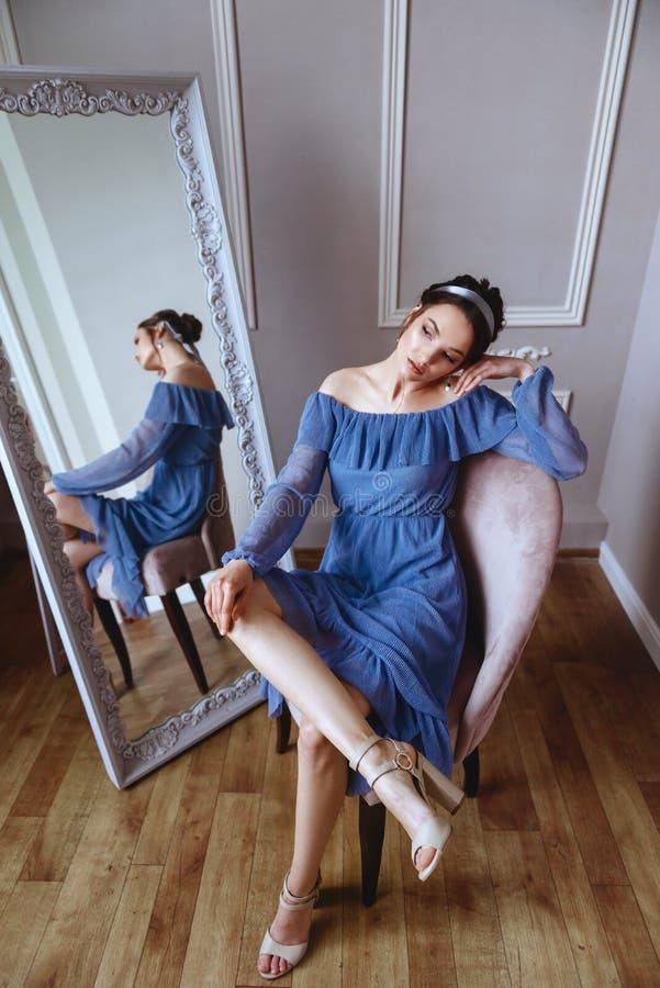 一件蓝色礼服的一美女坐天鹅绒扶手椅子 免版税库存照片