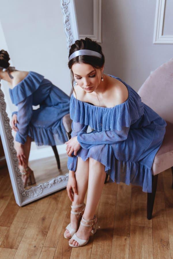 一件蓝色礼服的一美女坐天鹅绒扶手椅子 图库摄影