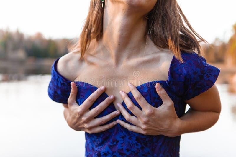 一件蓝色礼服的年轻女人握她的乳房作为自已援权的标志 库存图片