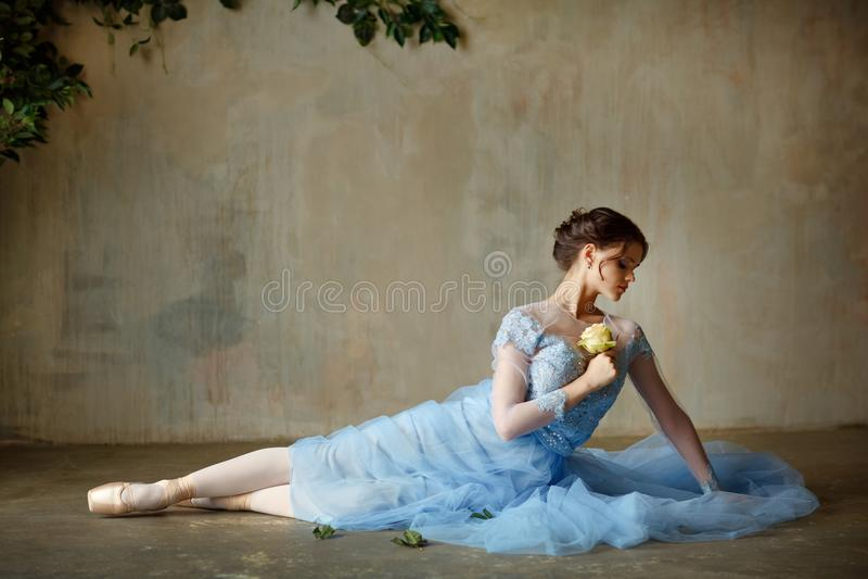 一件蓝色礼服的美丽的优美的女孩芭蕾舞女演员和pointe坐 免版税库存照片