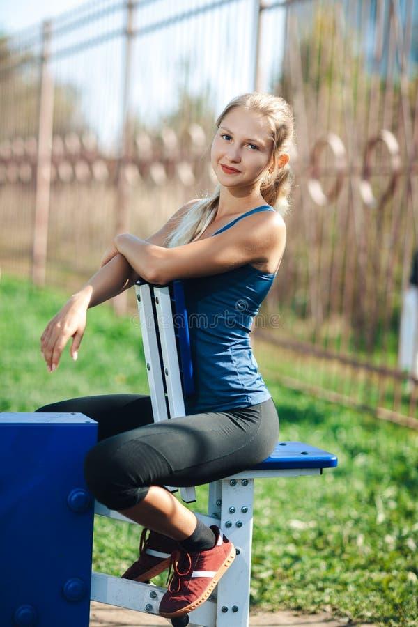 一件蓝色衬衣和绑腿的健身少妇使用室外健身房设备在看照相机和微笑的公园 免版税库存照片