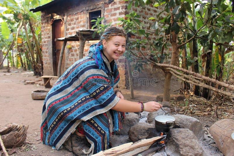 一件蓝色雨披的年轻嬉皮妇女烹调在一个营火营地的在村庄 库存照片