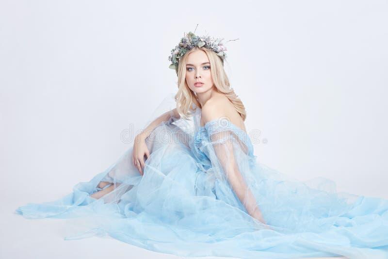 一件蓝色飘渺礼服和一个花圈的迷人的神仙的妇女在她的在白色背景,柔和的神奇白肤金发的女孩的头 库存照片