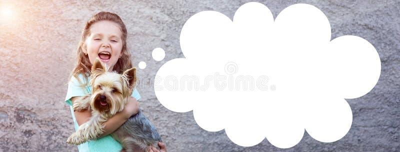 一件蓝色T恤杉的一个逗人喜爱的女孩有在她的举行狗和微笑的面颊的笑涡的 库存照片