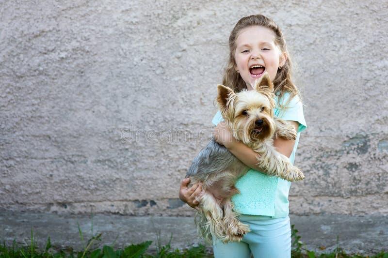 一件蓝色T恤杉的一个逗人喜爱的女孩有在她的举行狗和微笑的面颊的笑涡的 免版税图库摄影