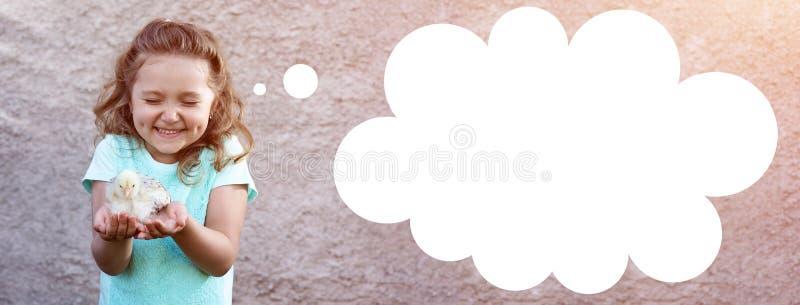 一件蓝色T恤杉的逗人喜爱的女孩有在她的面颊的笑涡的在她的手和半眯着的眼睛上拿着一只鸡以情感和欢欣 免版税库存照片