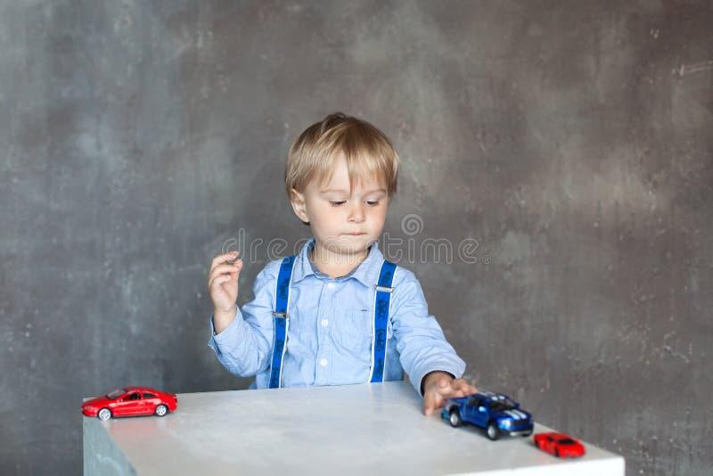 一件衬衣的一个小男孩有悬挂装置的使用与玩具多色的玩具汽车 使用与在桌上的玩具汽车的学龄前男孩在ho 图库摄影
