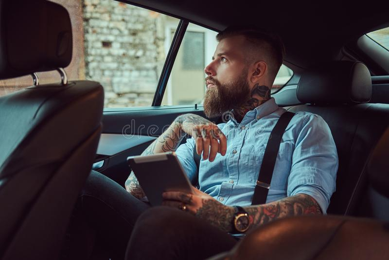 一件衬衣的古板的被刺字的行家人有悬挂装置的,拿着片剂,当在豪华汽车坐后面时 库存照片