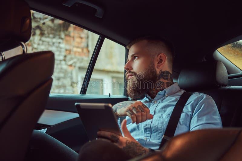 一件衬衣的古板的被刺字的行家人有悬挂装置的,拿着片剂,当在豪华汽车坐后面时 免版税库存图片