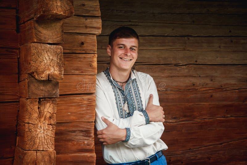 一件被绣的衬衣的美丽的年轻人在一个木房子的背景 免版税库存照片