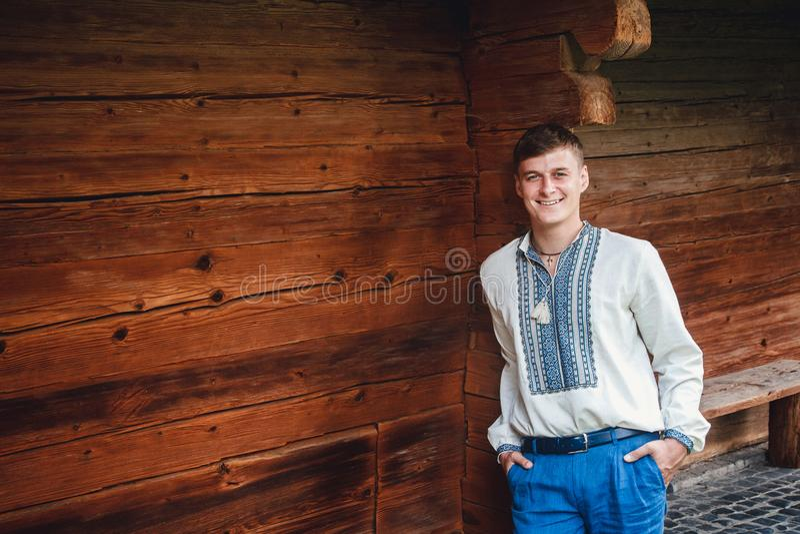 一件被绣的衬衣的美丽的年轻人在一个木房子的背景 免版税库存图片
