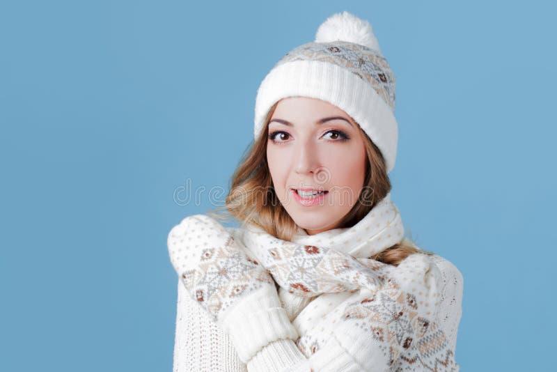 一件被编织的毛线衣的年轻和可爱的妇女,围巾,帽子,蓝色背景 免版税库存图片