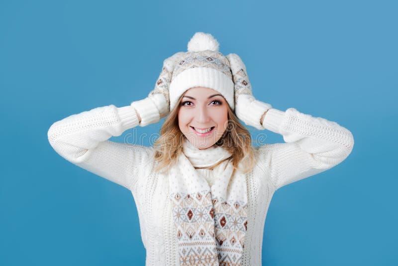 一件被编织的毛线衣的年轻和可爱的妇女 拉扯加盖,蓝色背景 免版税库存照片