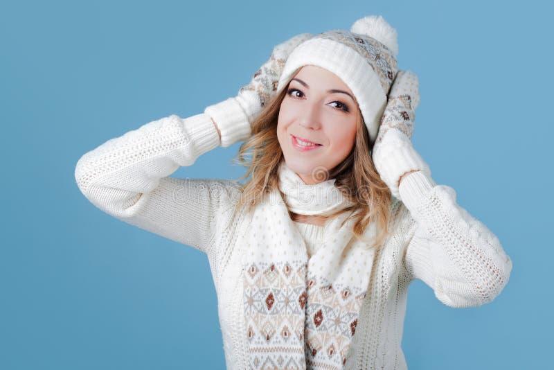 一件被编织的毛线衣的年轻和可爱的妇女 拉扯加盖,蓝色背景 库存图片