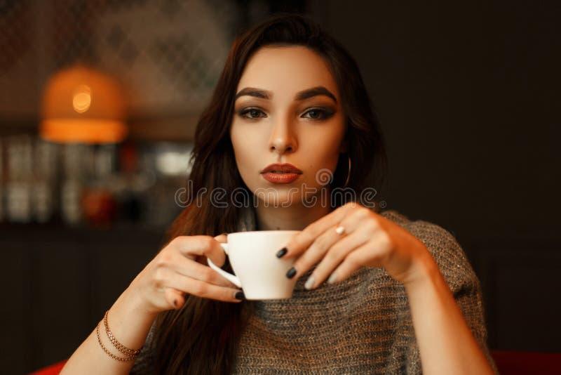 一件被编织的毛线衣的年轻美丽的妇女喝可口 库存照片