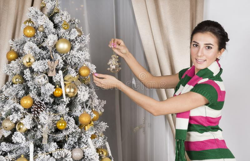 一件被编织的礼服的白女孩装饰圣诞树与 免版税库存照片