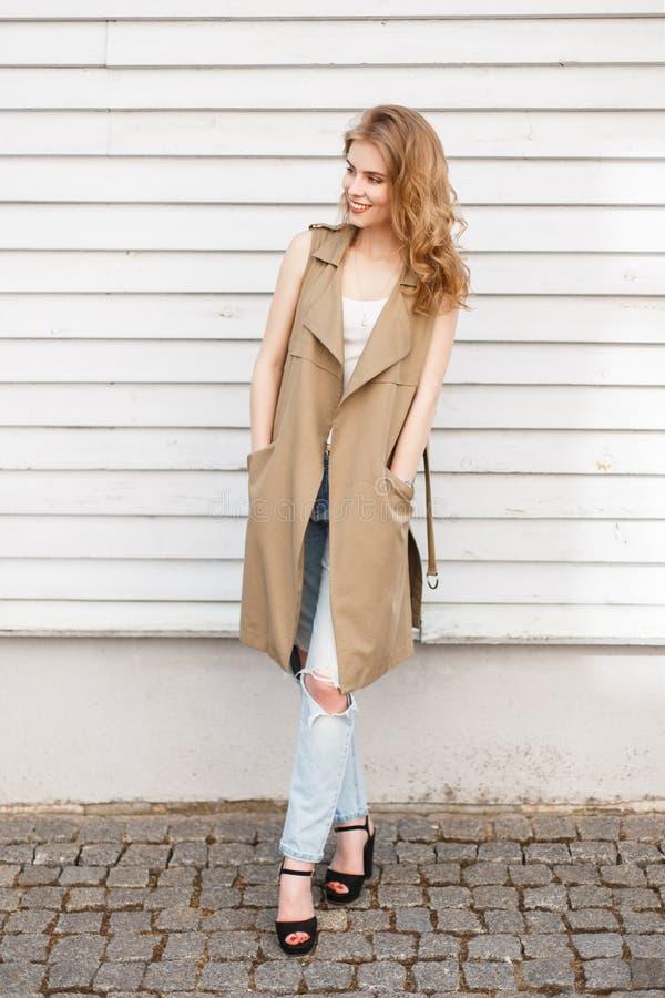 一件轻的夏天背心的迷人的快乐的年轻女人在蓝色被剥去的牛仔裤的一件时髦的T恤杉在有高跟鞋的黑鞋子 库存图片