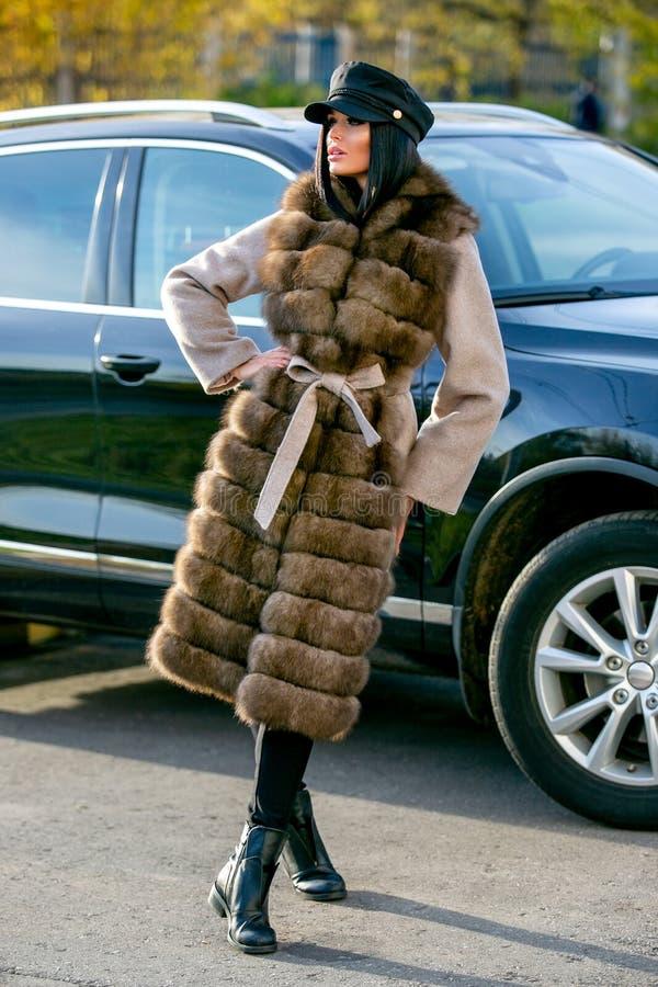 一件轻的外套的一个美丽的浅黑肤色的男人有毛皮、黑长裤和一个黑盖帽的在一辆汽车附近站立在一个秋天晴天, sexua 免版税库存图片