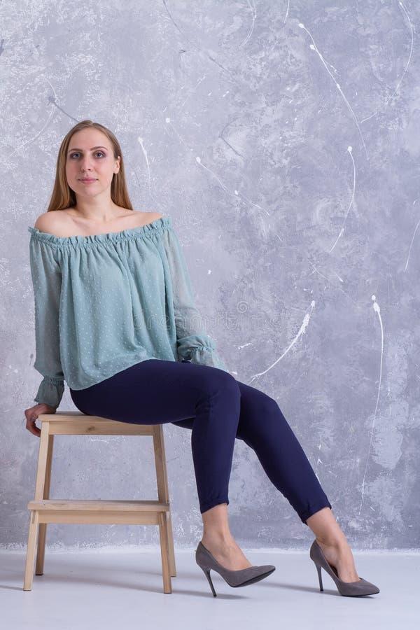 一件轻的女衬衫和裤子的美丽的白肤金发的女孩坐椅子 免版税库存照片