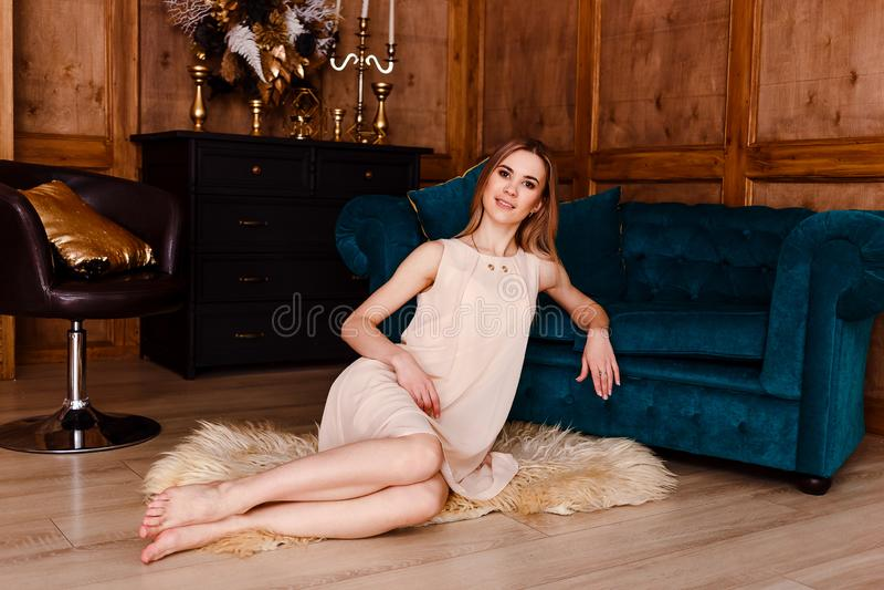 一件轻的米黄礼服的白种人年轻女人坐一个蓬松地毯在一个绿色沙发附近 免版税库存图片
