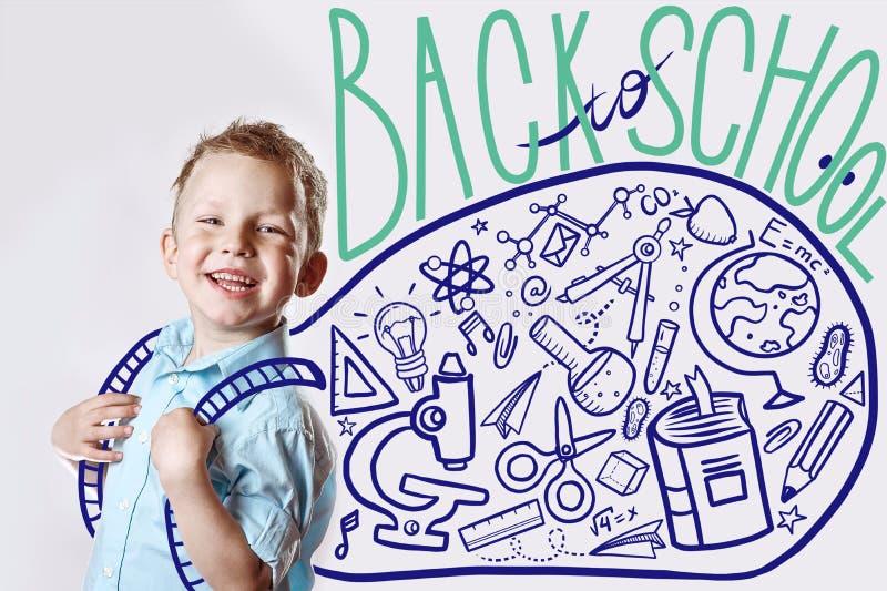 一件轻的衬衣的愉快的孩子去第一次教育 在他后是各种各样的象的背包 免版税库存照片
