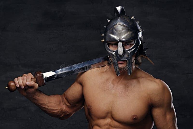 一件银色争论者盔甲的一个人拿着铁剑 库存图片