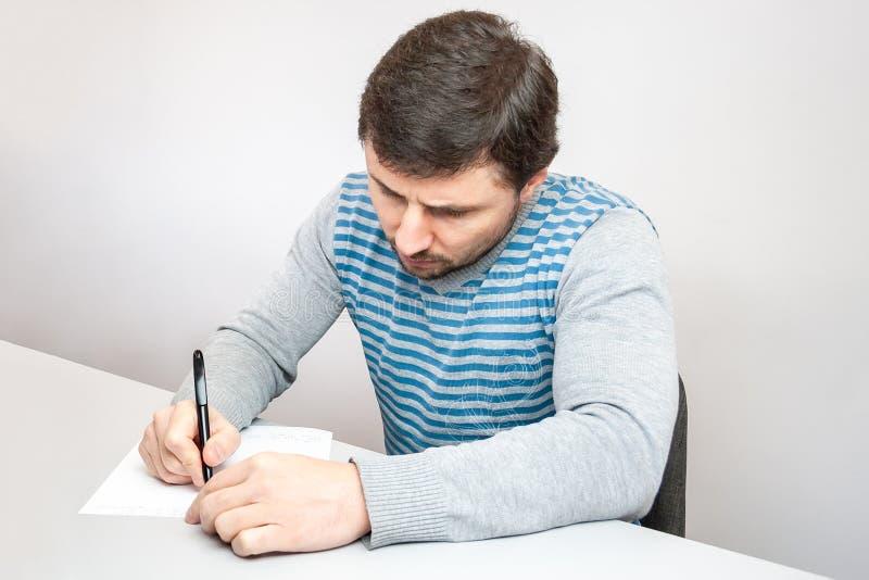 一件镶边毛线衣的英俊的体贴的人坐在桌上并且写与笔在纸 免版税库存图片