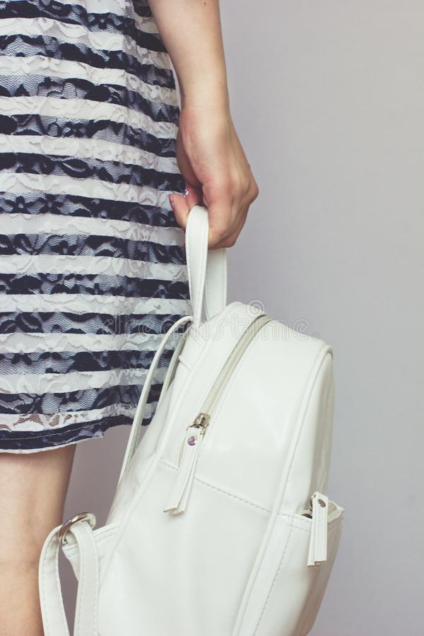 一件镶边礼服的女孩拿着一个白色背包 图库摄影