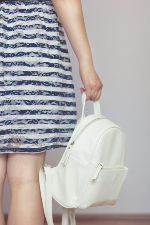 一件镶边礼服的女孩拿着一个白色背包 免版税图库摄影