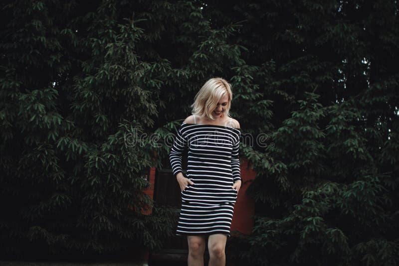 一件镶边礼服的时髦的有趣的白肤金发的女孩在木篱芭和冷杉木厚实的树篱  乐趣和逗人喜爱的微笑 免版税库存照片