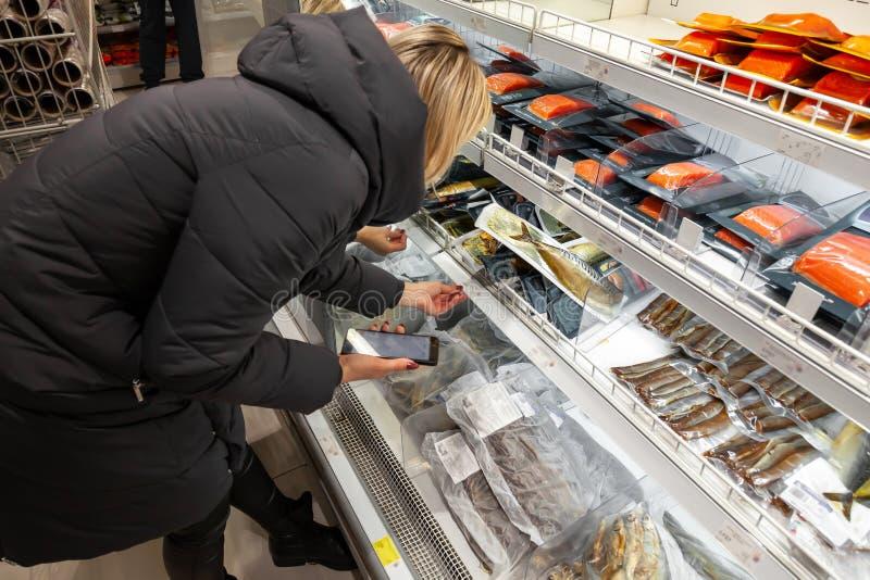 一件长的夹克的一个少女金发碧眼的女人选择食物一会儿购物 库存图片