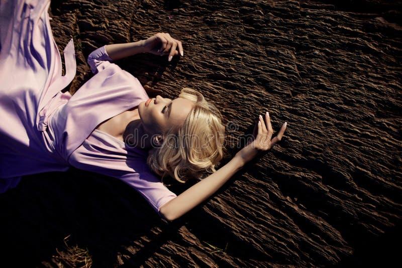 一件长的桃红色礼服的白肤金发的妇女坐石头在瀑布附近 华美的在女孩的面孔的长发美好的微笑 免版税库存照片