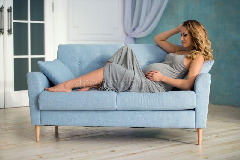 一件长的灰色礼服的美丽的愉快的年轻孕妇在家坐长沙发沙发 免版税库存照片