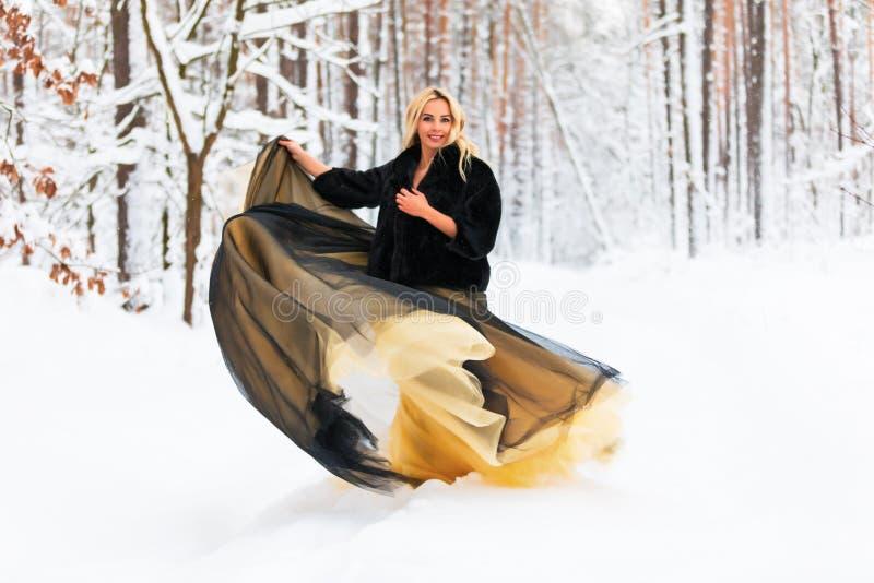 一件长的礼服的少妇在冬天森林里 免版税库存图片