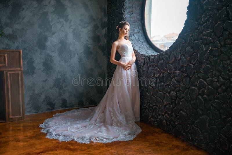 一件长的礼服的美丽的新娘由窗口 库存照片