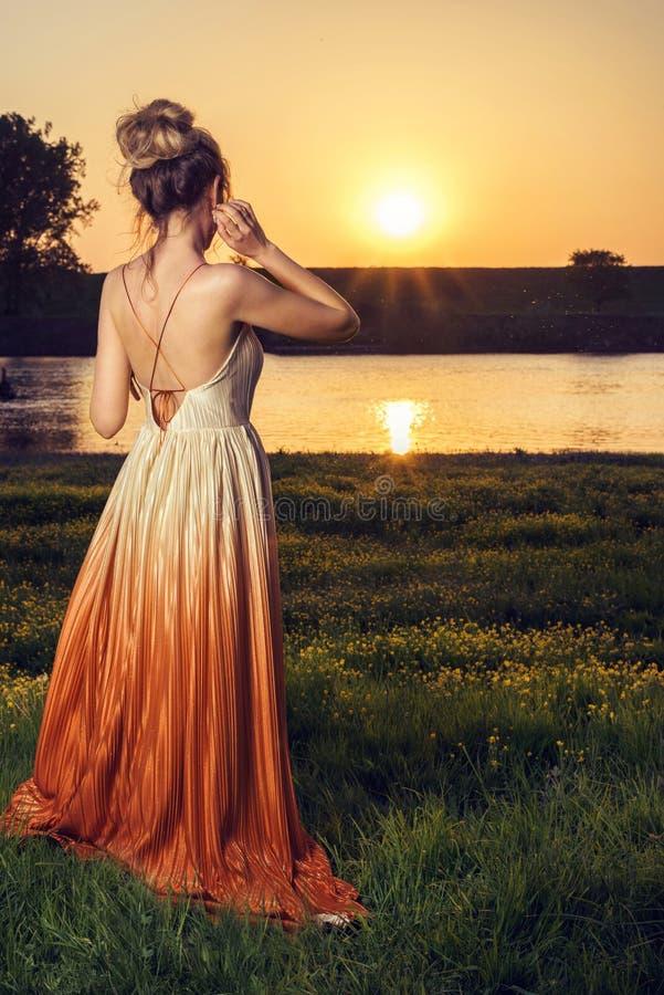 一件长的迷人的礼服的妇女在日落 美好的风景视图,从后面的射击 免版税库存照片