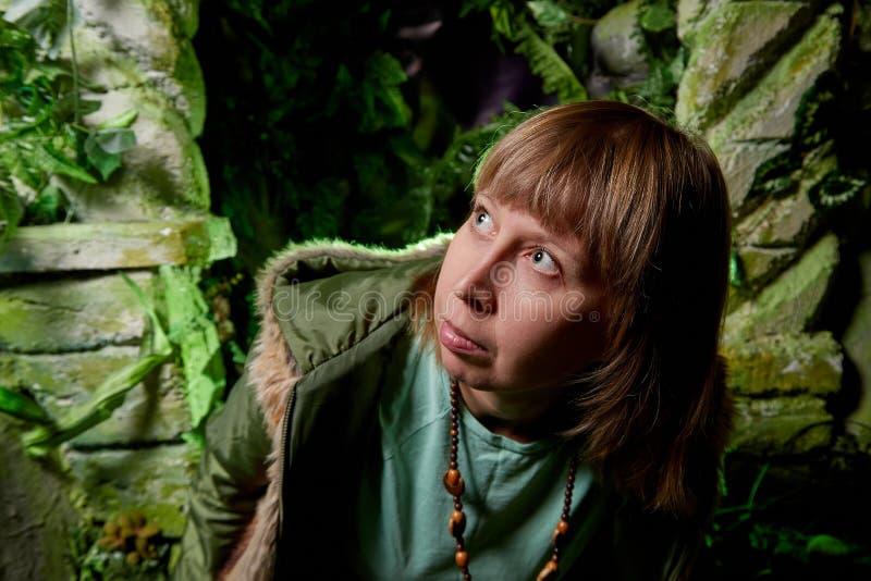 一件高尔夫球外套的女孩有在一个人为岩石附近的金发的与洞穴 美妙的照片写真在演播室 免版税库存照片