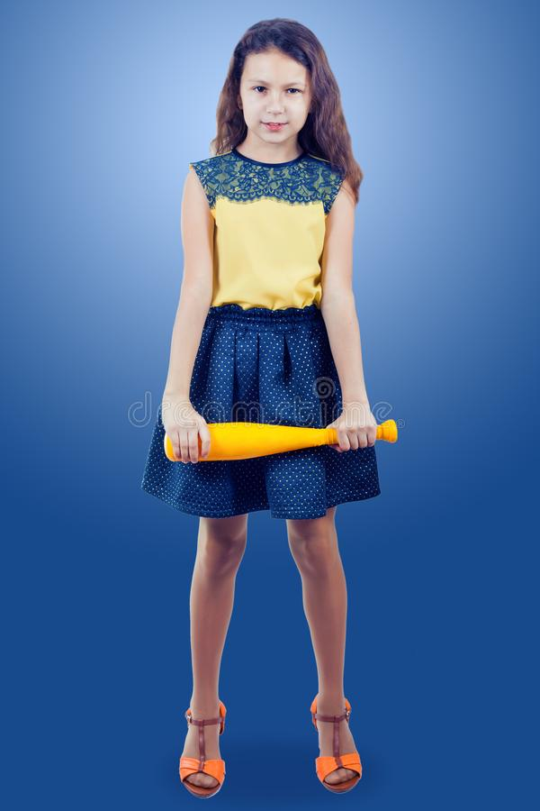 一件黄色女衬衫的小女孩有一个黄色玩具棒球棒的 库存照片