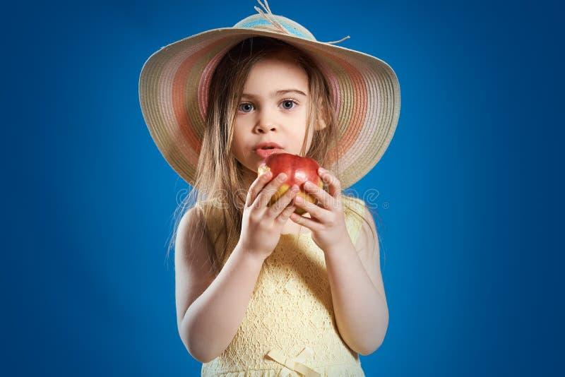 一件黄色礼服的可爱的小女孩吃一个美味红色苹果的 库存图片