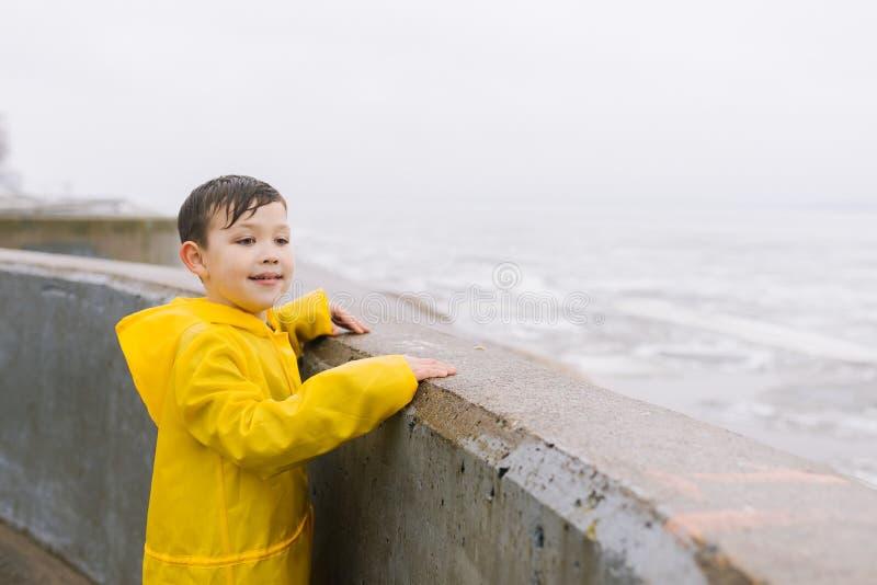 一件黄色雨衣的一个男孩看水表面湖,海,河,海洋 库存图片