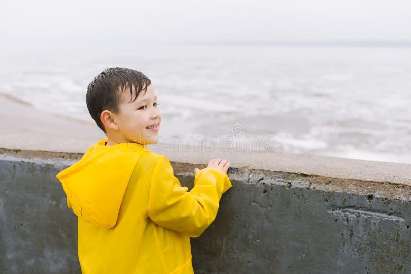 一件黄色雨衣的一个男孩看水表面湖,海,河,海洋 免版税库存照片