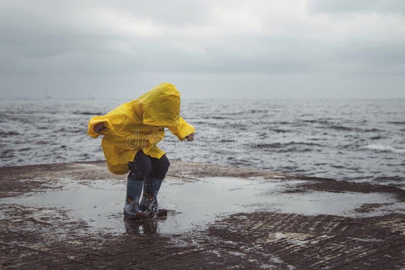 一件黄色雨衣跃迁的一个男孩在水坑 免版税库存照片
