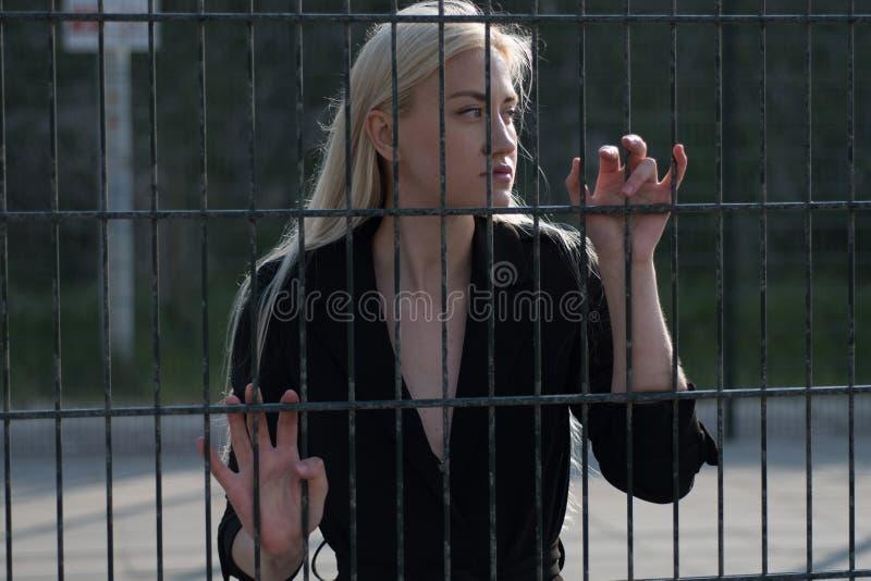 一件黑外套的白肤金发的女孩在金属篱芭后 库存图片