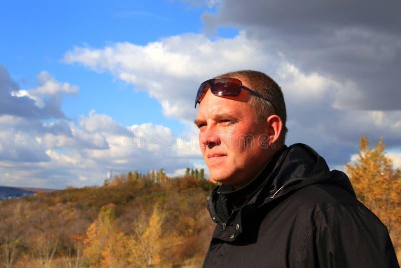 一件黑夹克和太阳镜的一个35-40岁游人看 免版税图库摄影