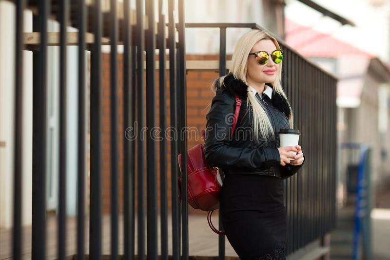 一件黑夹克和玻璃的美丽的女孩 免版税库存图片