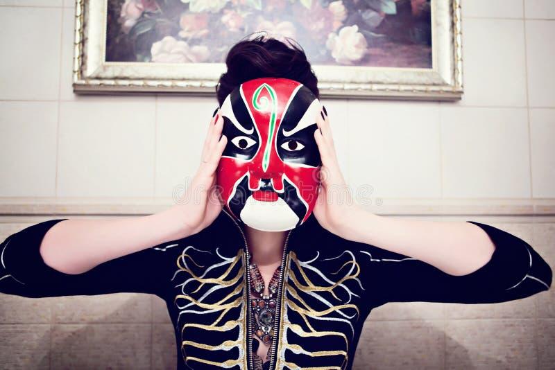 一件黑夹克的女孩有金刺绣和种族红白面具的 库存图片