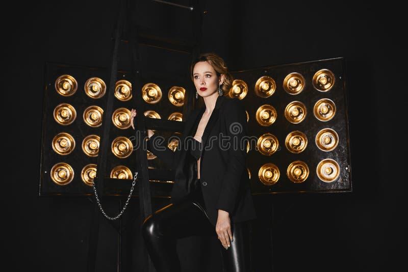 一件黑夹克的美丽,性感,时兴的半裸体的白肤金发的摆在与在背景的演播室灯的女孩和绑腿 免版税库存图片