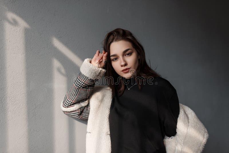 一件黑时髦的衬衣的可爱的年轻深色的妇女在有白色毛皮的一件时兴的格子花呢披肩夹克享用明亮的太阳 免版税库存图片